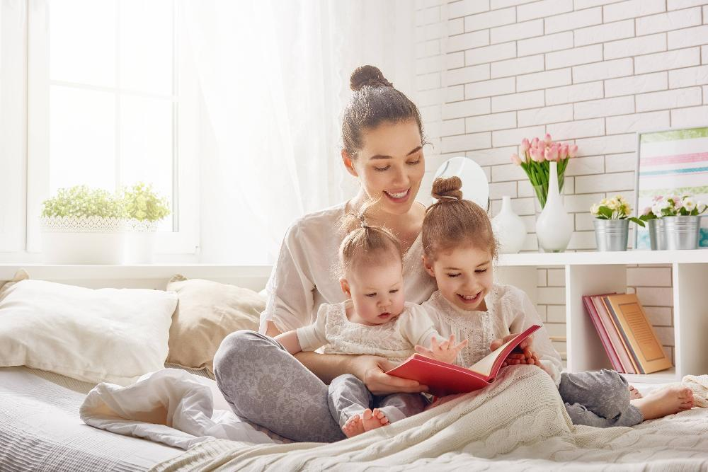 woman reading to two kid in bed l children's dentist near me